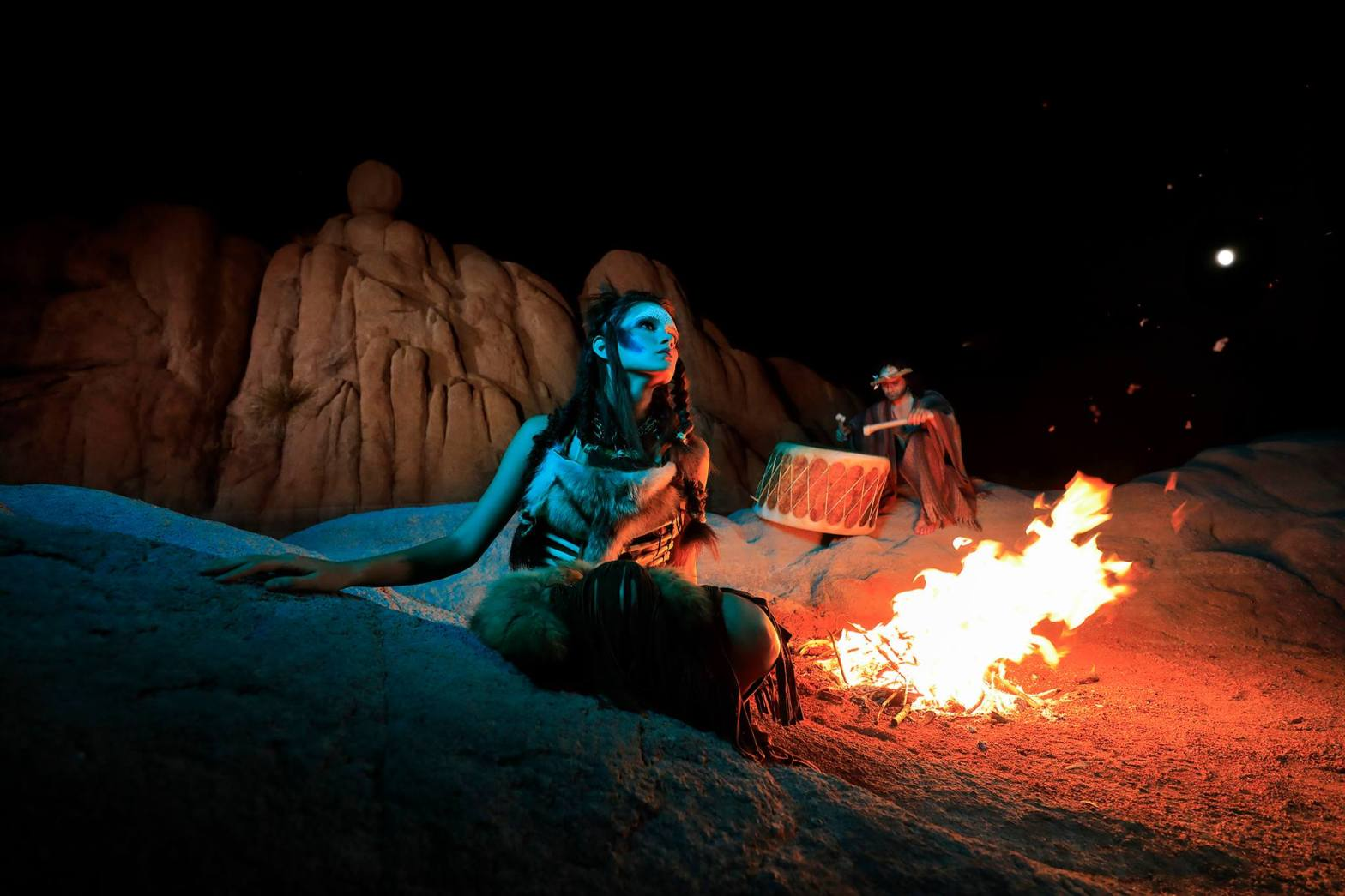 Clan of the Cave Bears model Samantha White poses in the foreground, Stevie Thunder on the drums behind her and the bonfire.